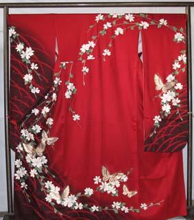 エンジ色にローケツ染めと金銀箔で描かれた蝶の柄がデザインされた現代的な振袖。