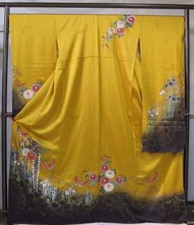 山吹色の生地に御殿まりと花が光沢のある占領で描かれた振袖。